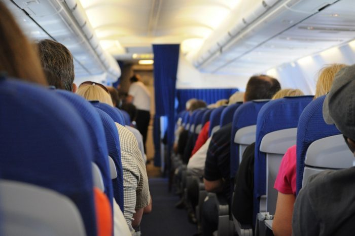 An aisle in an airplane full of people.