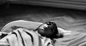 Person lying in bed, eyes closed.