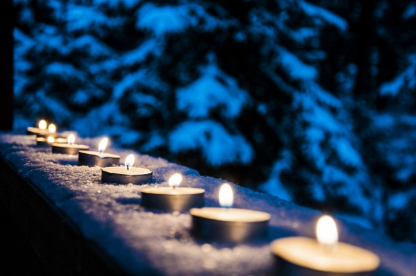 Image of candles lit up on a snowy ledge.